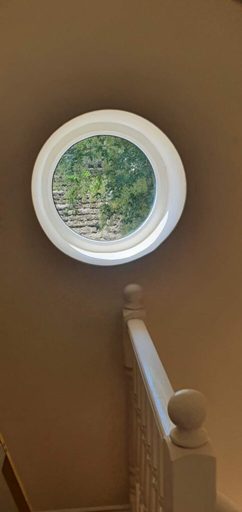 Fully round white timber look windows bringing light into a stairwell